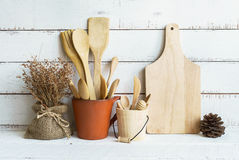 Kitchen cooking utensils on a shelf. With white rustic wooden background Stock Images