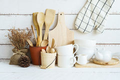 Kitchen cooking utensils on a shelf. With white rustic wooden background Stock Photos