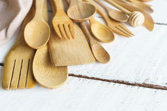 Kitchen cooking utensils on a shelf. With white rustic wooden background Stock Photo