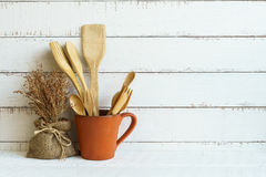Kitchen cooking utensils on a shelf. With white rustic wooden background Royalty Free Stock Image