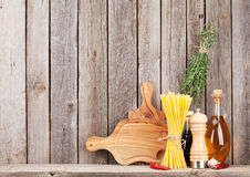 Kitchen cooking utensils and spices on shelf. Against rustic wooden wall with copy space Royalty Free Stock Photos
