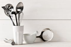 Kitchen cooking utensils in white cup with pestle and mortar on Royalty Free Stock Image
