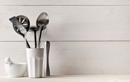 Kitchen cooking utensils in white cup with pestle and mortar on. White table with white wooden board background Stock Image
