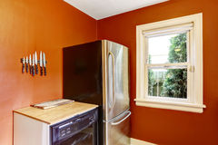Kitchen corner with bright red walls and steel refrigerator Royalty Free Stock Photo