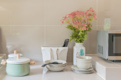 Kitchen counter with ceramic bowl, pot, plates. And vase of flower on garnite top counter Stock Image