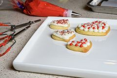 Kitchen counter with cookie decorating items, white patter with heart shaped decorated sugar cookies stock photography