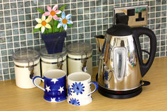 Kitchen counter with kettle and cups and flowers. Against a green tiled wall stock images