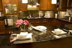 Kitchen counter setting home interiors. Elegant kitchen with marble counter top and beautiful plates Stock Image