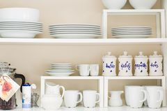 Kitchen cupboard, white porcelain dishes, tea pot, mugs and cups. Home related objects, ceramic objects are standing on kitchen shelf stock images