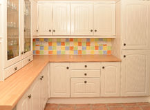 Kitchen cupboards. New kitchen showing cream colored wooden cupboards and drawers and large glass fronted cupboard for glasses, with multicolored tiled wall stock photography
