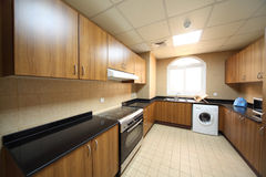 Kitchen with cupboards, washingmachine and cooker Royalty Free Stock Images