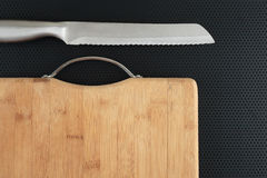 Kitchen cutting board and knife on a table Royalty Free Stock Photo