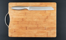 Kitchen cutting board and knife on a table Stock Photos