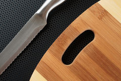 Kitchen cutting board and knife on a table Stock Photography