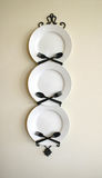 Kitchen Decoration. Of three white plates with criss-crossed knives and forks stock photos