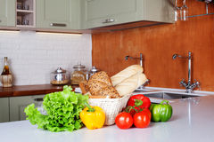 Kitchen design light fresh vegetables, bread basket, lettuce, peppers, tomatoes, shopping, cooking two sinks with Royalty Free Stock Photos