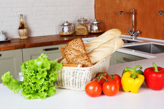 Kitchen design light fresh vegetables, bread basket, lettuce, peppers, tomatoes, shopping, cooking two sinks with Stock Images