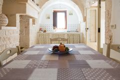 Kitchen and dining table in a an old trullo of Puglia, Italy. Vintage kitchen and dining table in a an old trullo of Puglia, Italy royalty free stock images
