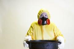 Kitchen disaster, hazmat suit. Mature woman in yellow hazmat suit  holding roasting pan Royalty Free Stock Photo