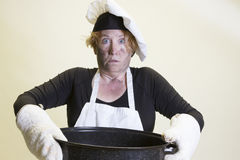 Kitchen disasters, roasting pan and chefs hat. Mature woman with singed face holding roasting pan with chefs hat and apron Royalty Free Stock Image