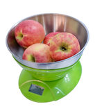 Kitchen electronic scales weigh several red apples. Royalty Free Stock Photo