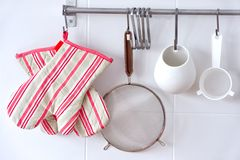 Kitchen equipement. Rack of kitchen utensils and oven gloves Stock Photography