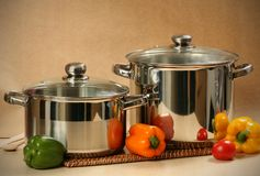 Kitchen equipment. Two pans and vegetables closeup royalty free stock images
