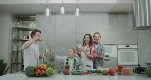 In the kitchen family spending a good time together playing with bubbles and dancing before making the healthy breakfast stock video footage