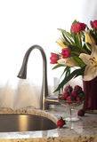 Kitchen faucet, strawberries and fresh flowers on a counter. Royalty Free Stock Images