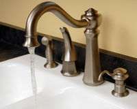 Kitchen Faucets. A new, white enamel kitchen sink with fancy, modern faucets. The water is on royalty free stock photo