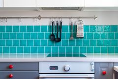 Kitchen features dark gray flat front cabinets paired with white quartz countertops and a glossy blue care tile. Stock Image
