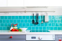 Kitchen features dark gray flat front cabinets paired with white quartz countertops and a glossy blue care tile. Royalty Free Stock Photography