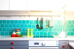Kitchen features dark gray flat front cabinets paired with white quartz countertops and a glossy blue care tile. Stock Photo