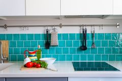 Kitchen features dark gray flat front cabinets paired with white quartz countertops and a glossy blue care tile. Royalty Free Stock Photos