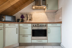 Kitchen of a flat. With oven, microwave, stove, hood, cabinets and wooden ceiling Royalty Free Stock Photography