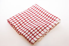 Kitchen folded towel in a cage on white. Kitchen towel folded in the red cell to white Royalty Free Stock Photo