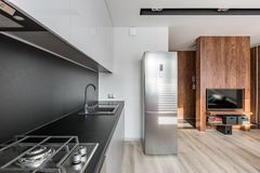 Kitchen open to tv room. Kitchen with fridge, black worktop and backsplash, open to tv room stock image