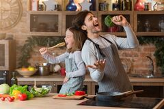 Free Kitchen Fun. Cheerful Dad And His Little Daughter Singing While Cooking Together Stock Photos - 184366513
