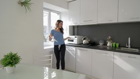 Kitchen fun, merry housewife woman dancing and sings with pan in hands while cooking meal at cuisine at home. In holiday stock video footage