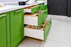 Kitchen furniture in green with open drawers stock photo