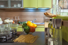 Kitchen furniture stone worktop with colored sweet peppers in gl Stock Photos