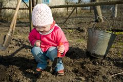 In  a  kitchen garden. A smiling  little girl squatting down on the ground  cultivating soil with  a toy  spade Stock Photos