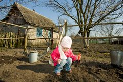 In  a  kitchen garden. A pretty little girl squatting down on the ground cultivating soil with  a toy  spade Royalty Free Stock Photos