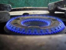 Kitchen gas stove burner flaming in dark blue color flames.  Nice to see it in closeup angle. Royalty Free Stock Image