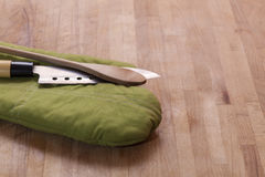 Kitchen glove with knife and spoon on wooden board. A green kitchen glove (pot holder) with knife and wooden spoon on a wooden table Royalty Free Stock Photos