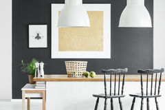 Kitchen with gold painting. Braided basket on wooden countertop and black bar stools in kitchen with gold painting on black wall royalty free stock photo