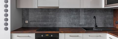 Kitchen with granite worktop and concrete backsplash. Panorama of new kitchen with granite worktop and concrete backsplash and functional cabinets stock images
