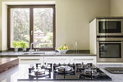 Kitchen granitic worktop with a cooker. And the kitchen units with oven close to the window behind the worktop in the foreground royalty free stock photography