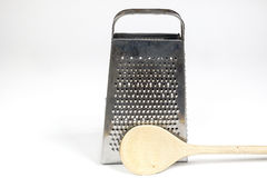 Kitchen grater with a wooden spoon on a white background Royalty Free Stock Image