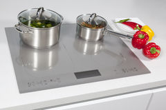 In the kitchen. Grey glass induction hob in the kitchen royalty free stock photography